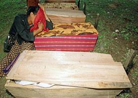Mulher chora sobre um dos seis caixões contendo os restos mortais de vítimas desenterrados em Maubara.
