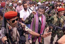 O comandante das Falintil, Xanana Gusmão, cercado por tropas de alta segurança, saúda a multidão na sua chegada numa cerimónia, realizada na sede das Falintil em Remexio.