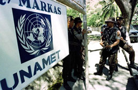 Policias de Brigada Moveis indonésios a aguardar a frente da sede da Missão de Assistência das Nações Unidas para Timor Leste (UNAMET) em Balide
