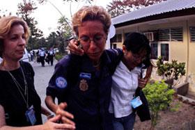 Uma policia da ONU (C) é consolada por colegas na chegada ao complexo da ONU em Díli, vindo de Liquiça